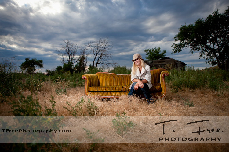 Smashing old grungy couch senior photo with blue sky in western Nebraska.