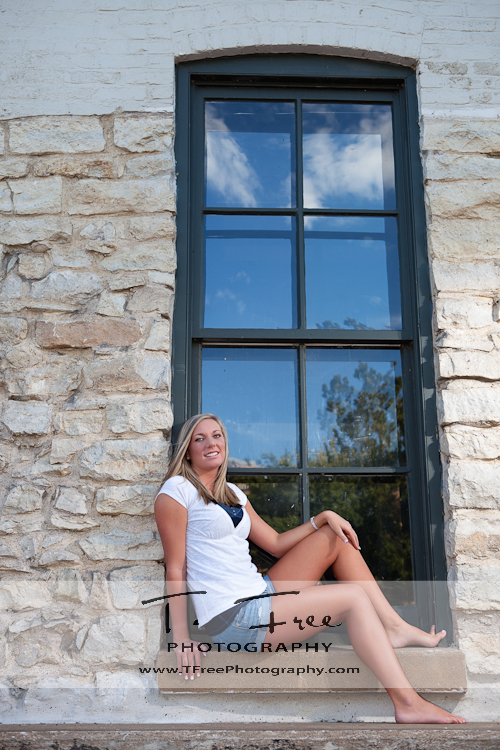 Outdoor senior picture in window of historic building at Gene Leahy Mall in downtown Omaha.