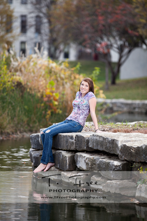 Stunning fun senior picture with green grass, trees, and water taken in downtown Omaha Nebraska.