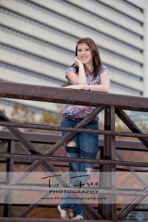Outdoor park photo of a high school senior on a bridge in downtown Omaha Nebraska.