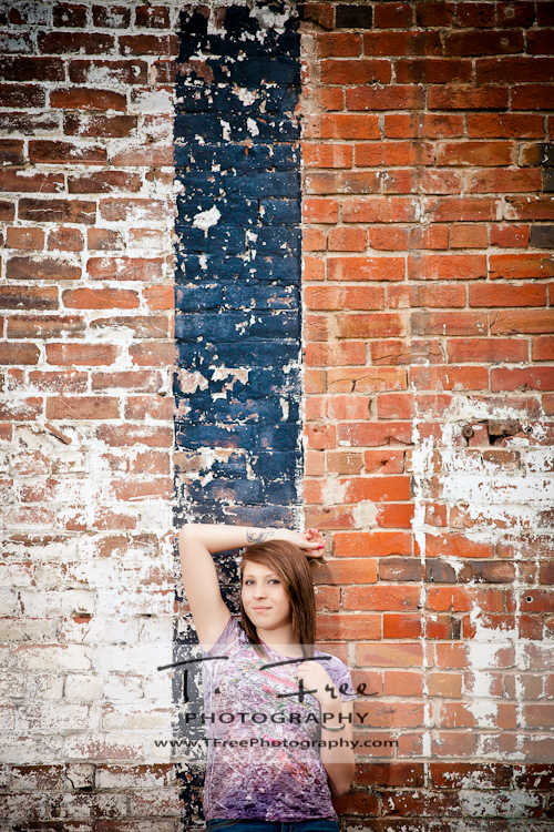 Cool senior picture in downtown Omaha Nebraska against an old brick building.