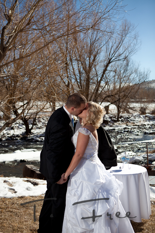 Scenic view of a Colorado river and mountains as the groom kisses his bride.