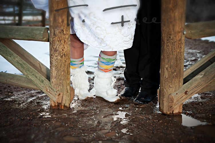 Bride and groom standing in the mud after snow melt on their wedding day.