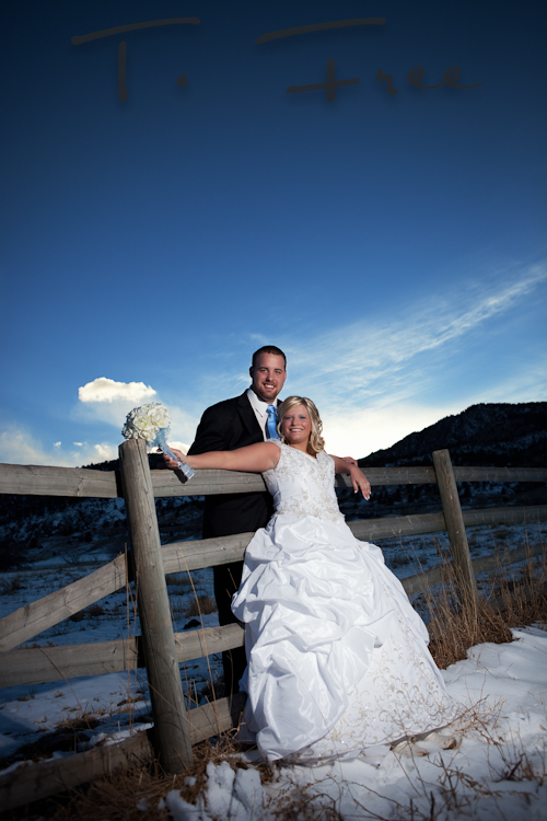 Bride and Groom leaning on a fence with a beautiful deep blue Colorado sky as the backdrop.