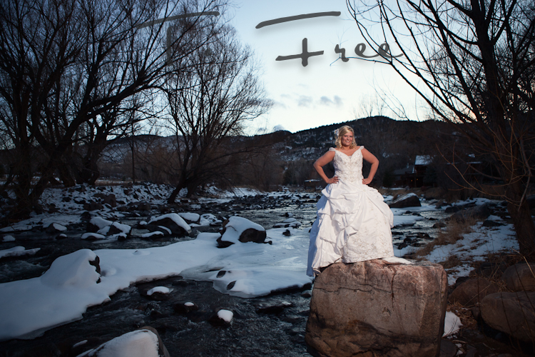 Stunning bridal photo standing on a boulder in a Colorado river.