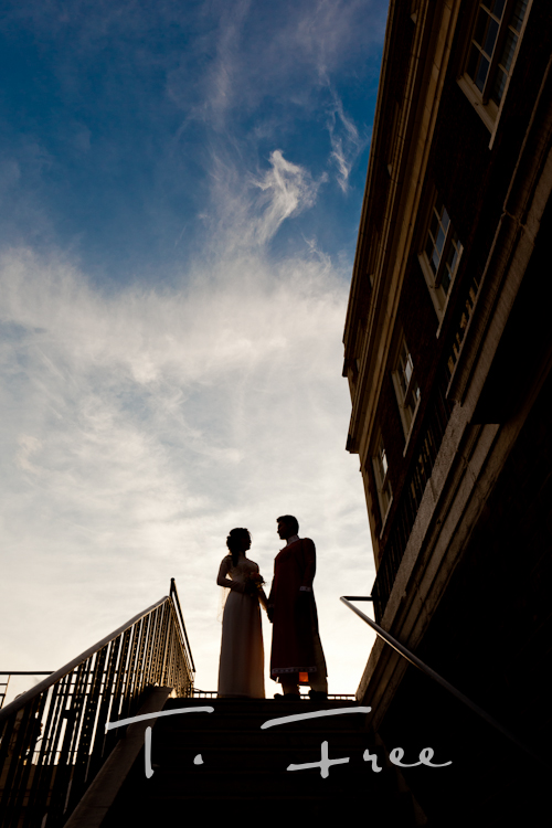 Outdoor big blue sky silhouette image of the vietnamese bride and groom at the Omaha Magnolia Hotel courtyard.
