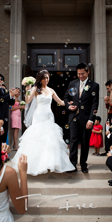 Vietnamese bride and groom exiting the church with bubbles after their wedding ceremony in Omaha Nebraska.