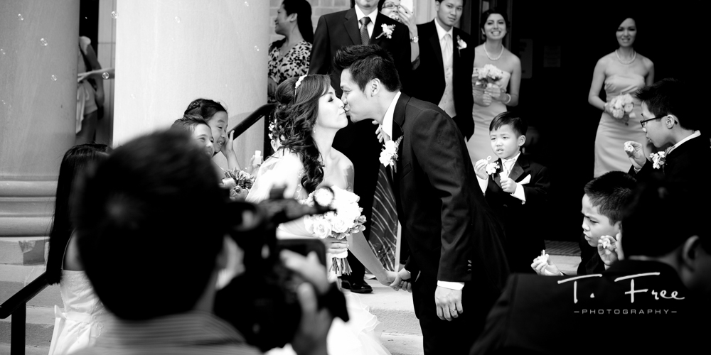 Bride and groom first kiss after their wedding ceremony exiting st. peter catholic church in omaha.