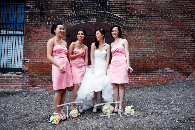 Cool natural outdoor bridesmaids image with the bride against an old brick building in Omaha.