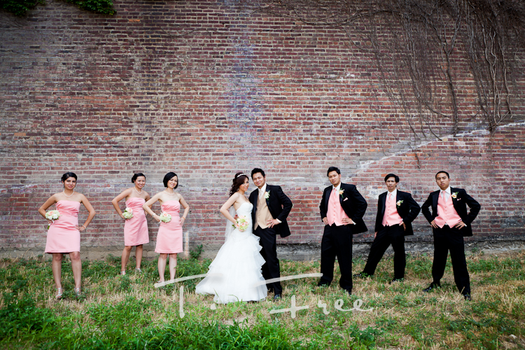 Creative outdoor wedding party photography against a red brick wall in downtown Omaha Nebraska.