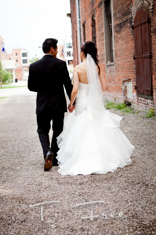 Gorgeous vietnamese bride and groom walking down an ally in Omaha.