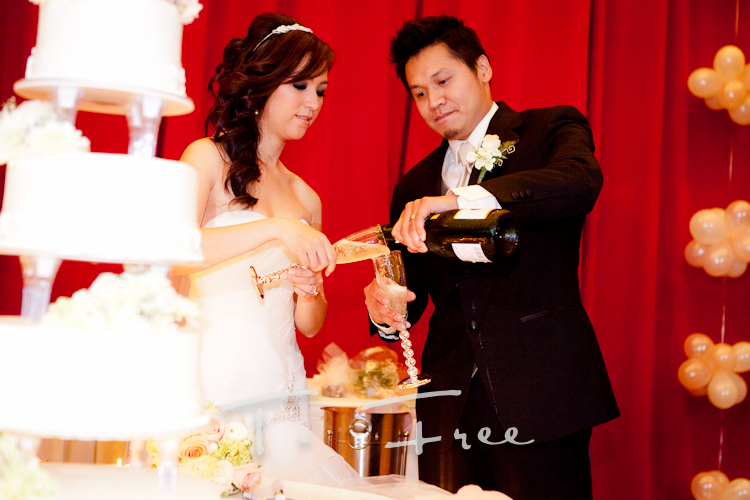 Vietnamese couple cutting their wedding cake and pouring champagne at their Harrah's Council Buffs reception.