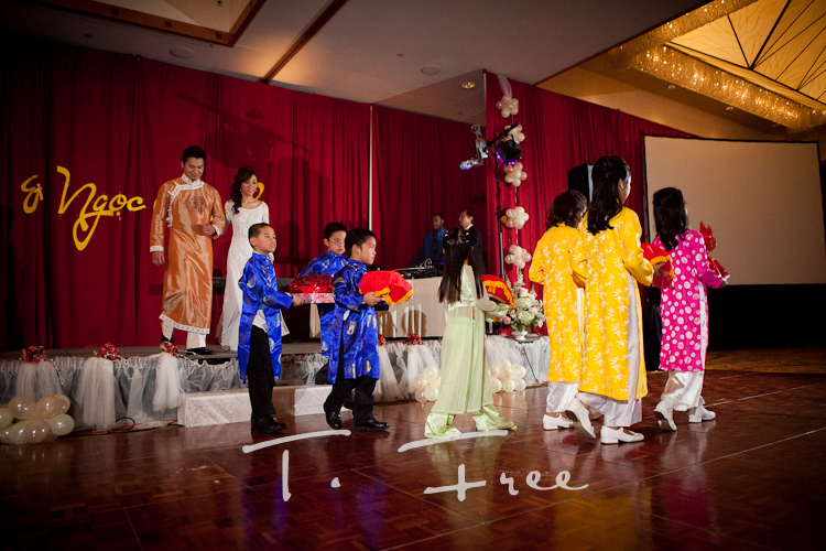 Vietnamese gifts being presented followed by the bride and groom in Omaha.
