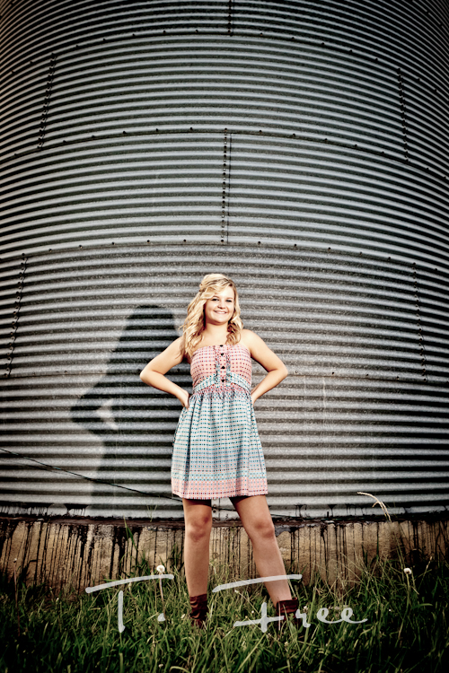 Outdoor on location senior picture of lincoln nebraska high school senior standing next to a grain bin.
