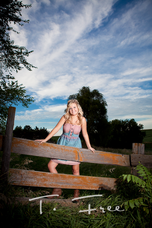 Rustic outdoor farm high school senior pictures on an old wooden fence.