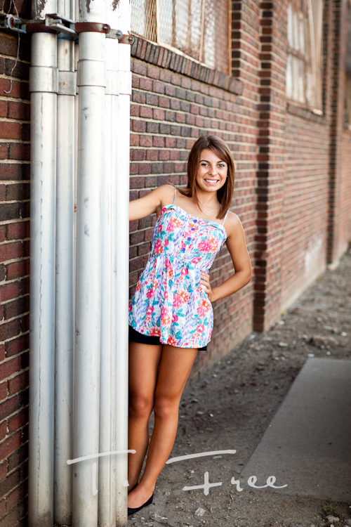 Leaning by a brick wall for her senior picture.
