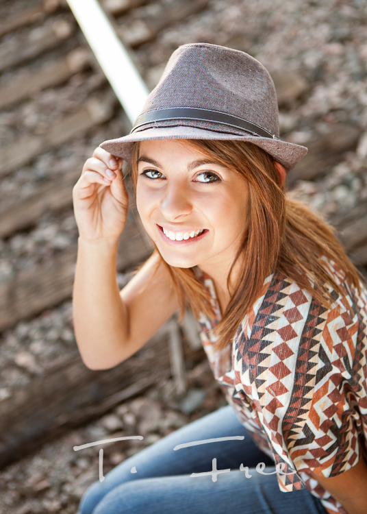 Outdoor natural light close up senior picture with a fedora hat in Omaha.