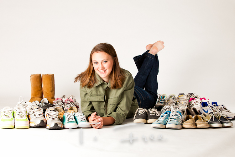 In studio senior picture with her closet full of shoes in Omaha, Nebraska.