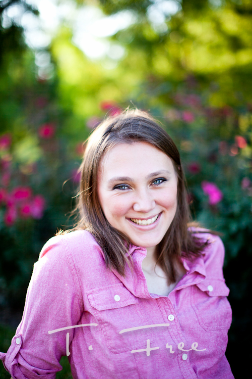 Gorgeous smiling senior picture with roses blurred in the background near Elkhorn.