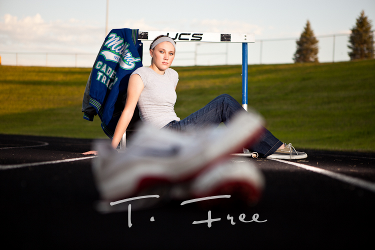 Creative senior picture with track shoes and hurdle and letter jacket taken near Elkhorn.