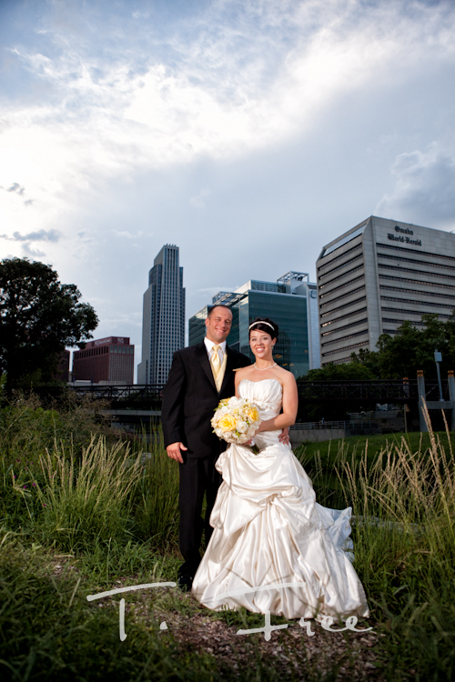 Bride and groom at Gene Leahy Mall area for an Omaha skyline image.
