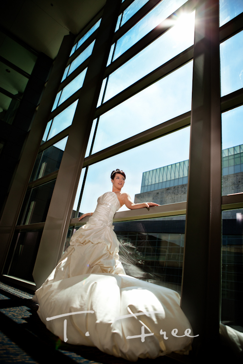 Cool bridal photo of bride and a large wall of glass at the Holland Performing Arts Center in downtown Omaha Nebraska.