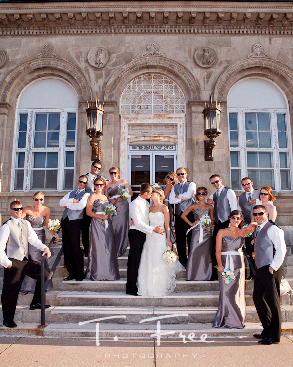 Very fun wedding party group photo with bride and groom kissing in downtown Holdrege Nebraska.