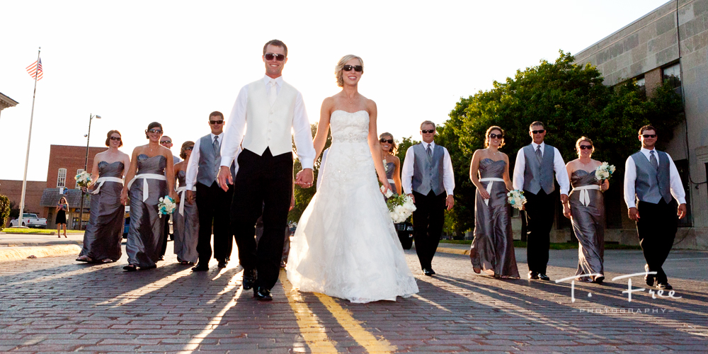 Cool photo of bride and groom leading their wedding party on downtown Holdrege Nebraska red brick streets.