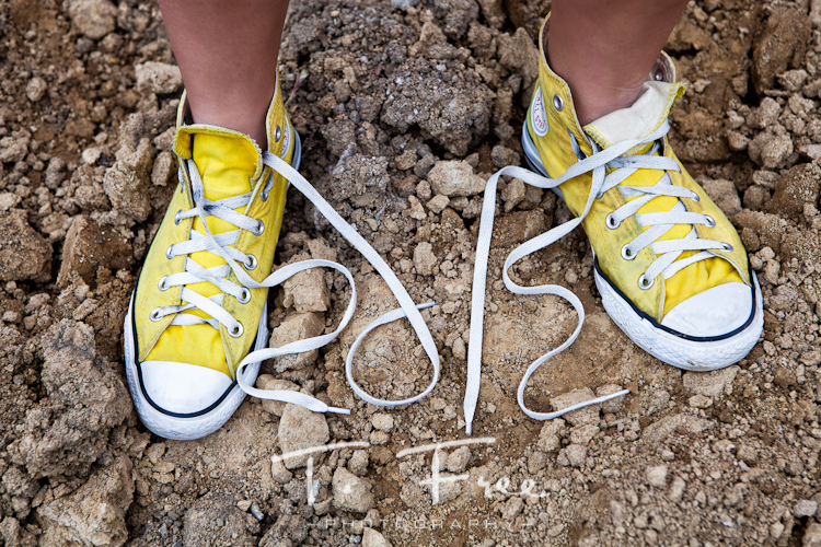 Yellow Chuck Taylor's with shoe laces spelling 2012 on senior photo shoot in downtown Omaha Nebraska.