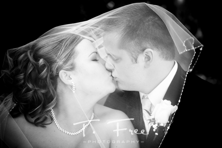 Stunning black and white image of bride and groom behind veil near Kearney Nebraska.