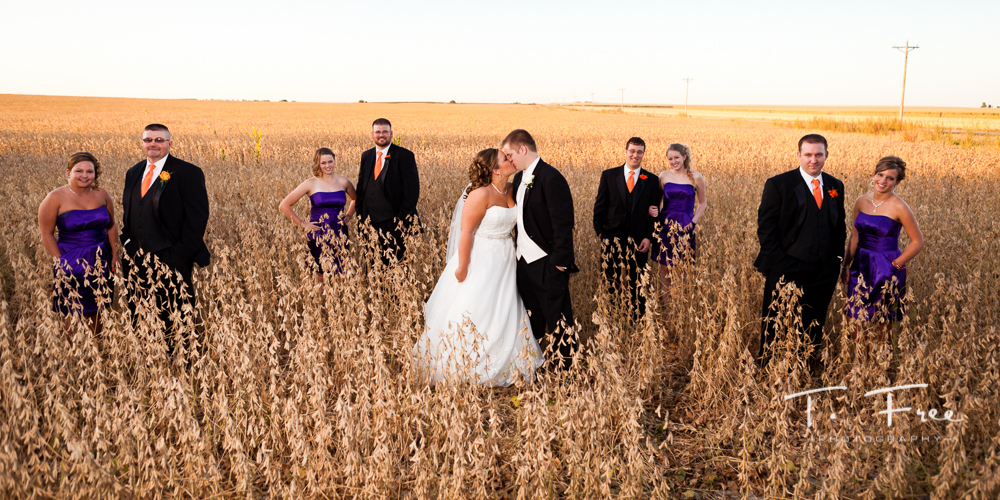 Cool photo of bride and groom with wedding party out in the country in a soybean field near Kearney Nebraska.