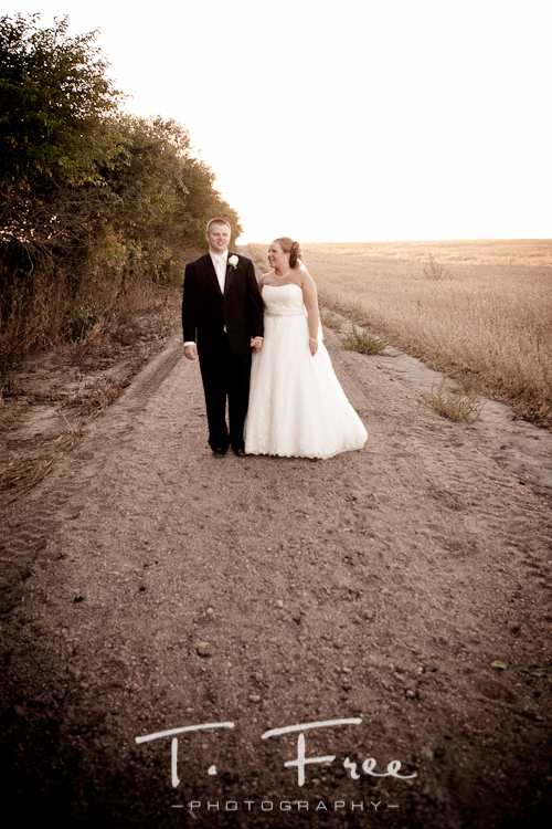 Bride and groom walking down a dirt road in the country in Nebraska.