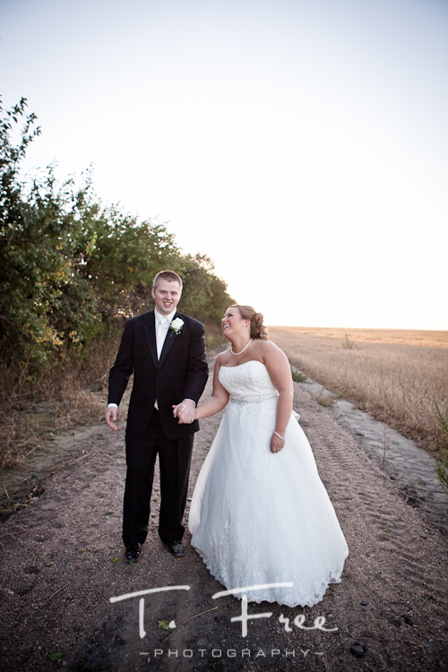 Bride and groom laughing walking down a dirt road in the country in Nebraska.