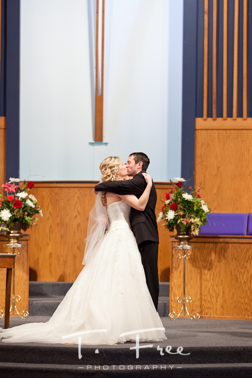 Newly married couple kissing at the altar at Harrison Street Baptist Church in La Vista Nebraska