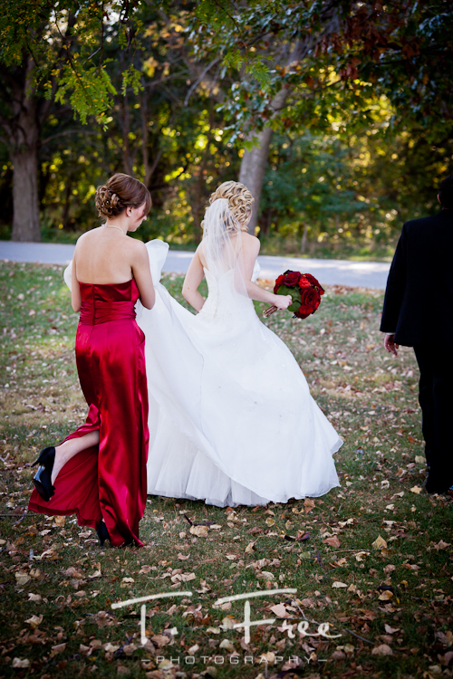 Brides sister carrying her wedding dress train in Omaha.