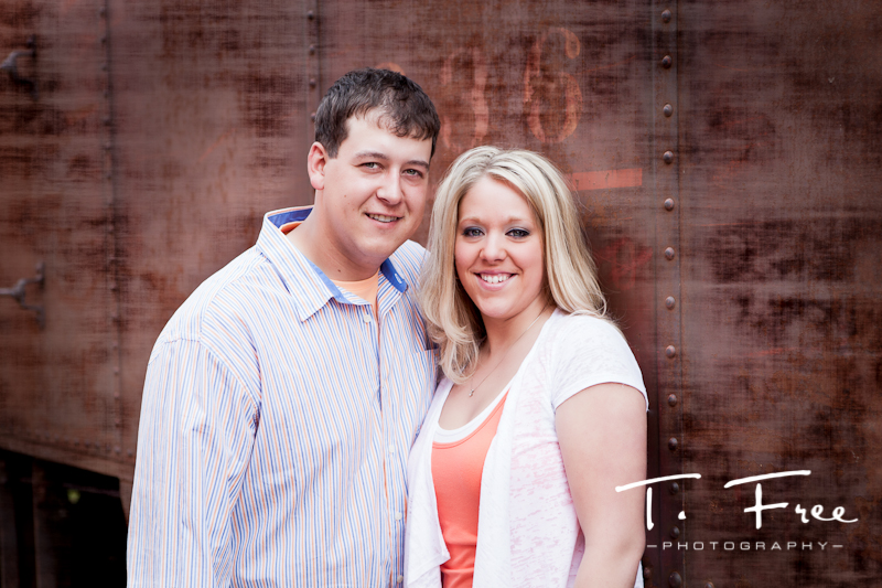 Engagement portrait outdoors with textured old train car near Hooper Nebraska.