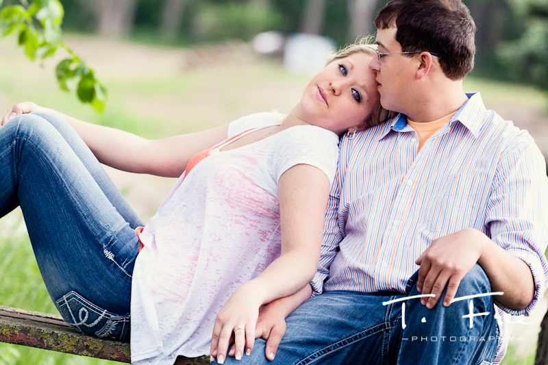 Engagement photograph of couple sitting on an old picnic table in Hooper Nebraska.