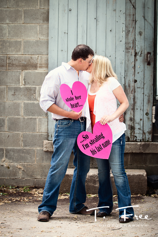 Cute rustic engagement photo with handmade signs by the bride taken near Omaha Nebraska.