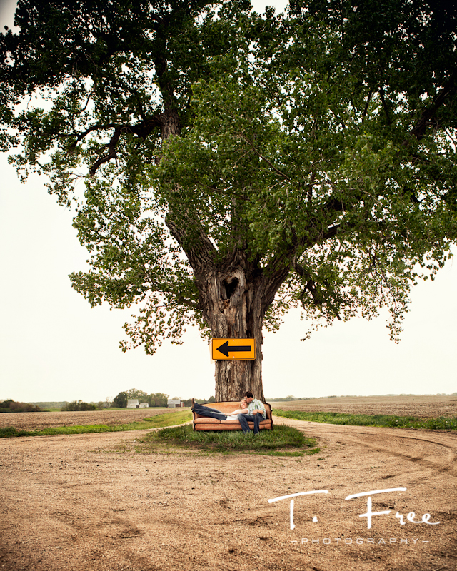 Unique creative outdoor engagement image with an old 1940 couch under a large tree in the middle of a road near Scribner Nebraska.