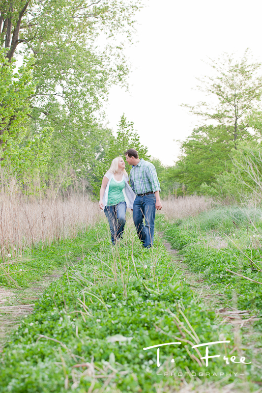 Outdoor engagement photo of couple walking along a path kissing at Dead Timber State Recreation Area near Scribner Nebraska.