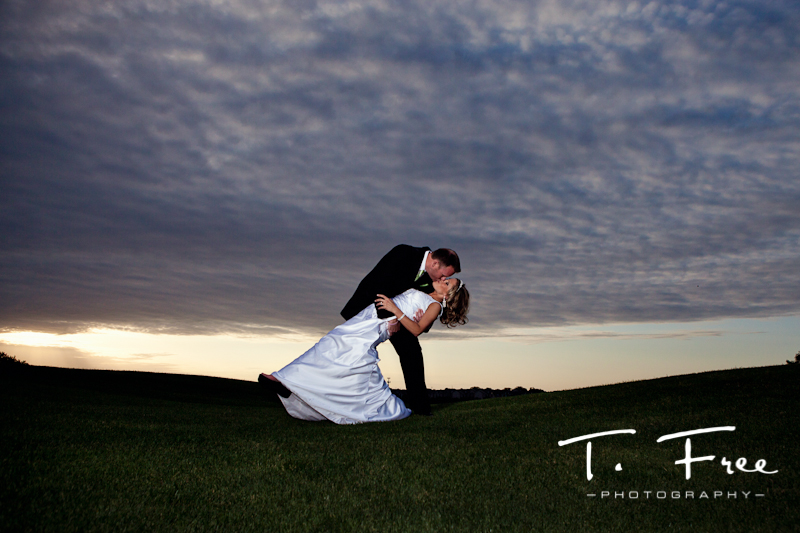 Very cool wow image of bride and groom kissing at Champions Run Omaha golf course at sunset.