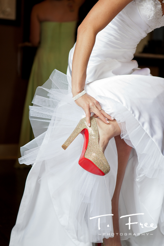 Bride putting on her Christian Louboutin wedding high heal shoes in historic downtown Elkhorn Nebraska.