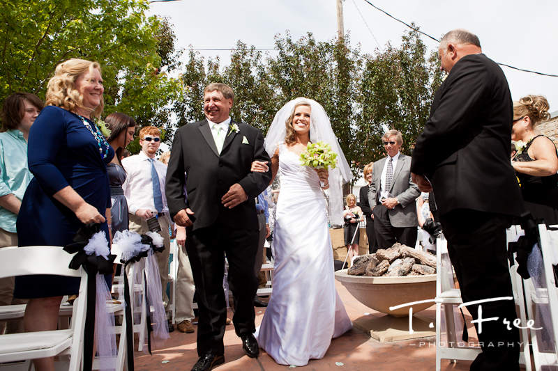 Bride coming down the aisle at her outdoor wedding in downtown Elkhorn Nebraska.