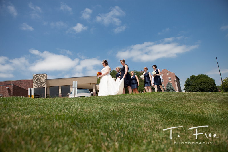 Deep blue sky image of bride with bridesmaids at Brownell-Talbot in Omaha Nebraska.
