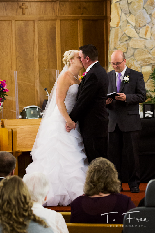 Bride and groom kissing at the alter.