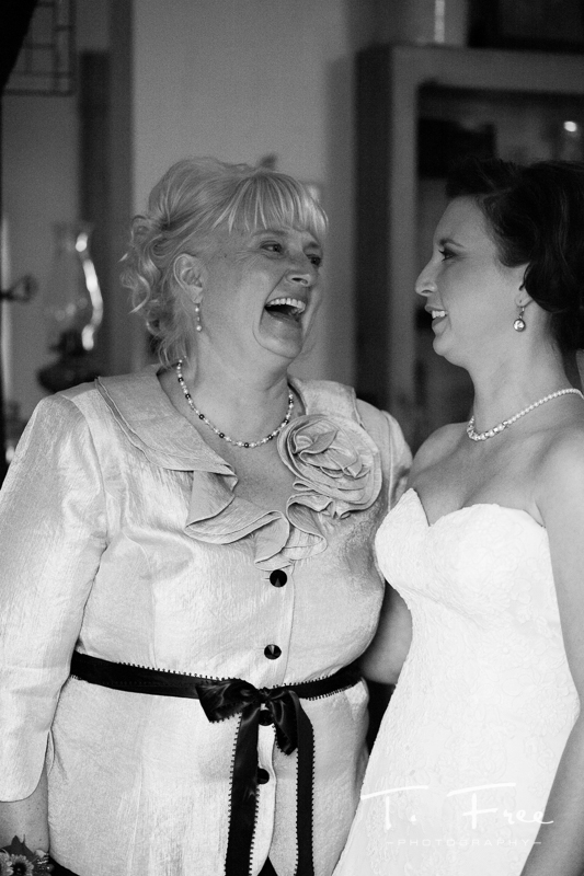 Bride and mother candid moment before Nebraska vineyard wedding.