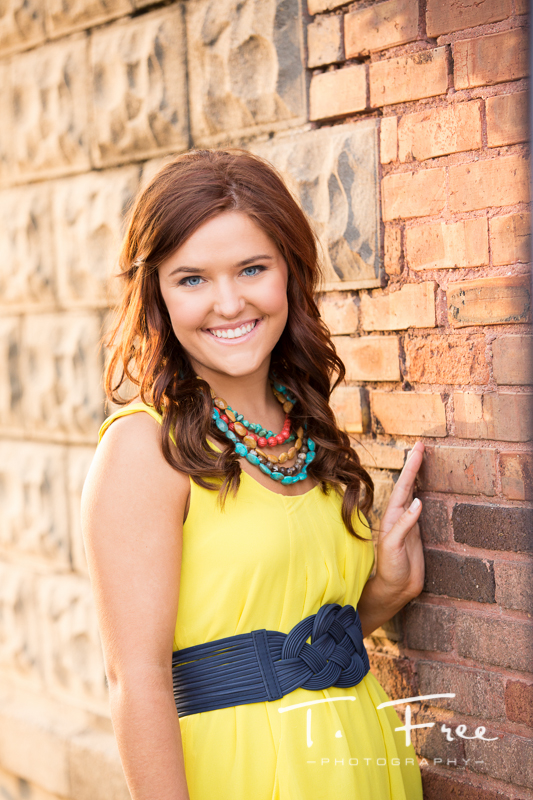 Vibrant yellow dress and necklace during omaha nebraska senior photo shoot.